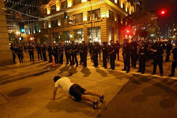A protester does pushups as Los Angeles police in riot gear pause while pushing the crowd back from 5th and Spring streets during the Art Walk melee.