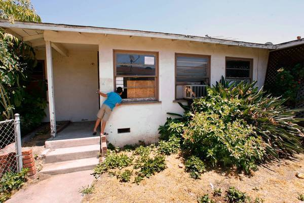 A neighbor peeks into an unoccupied, foreclosed home owned by US Bank in El Sereno.