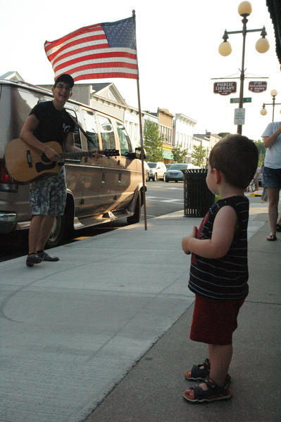 Singer David Kramp of Gaylord enchants Jackson Berry, 23 months, of Troy, during a recent Street Musique in Harbor Springs.