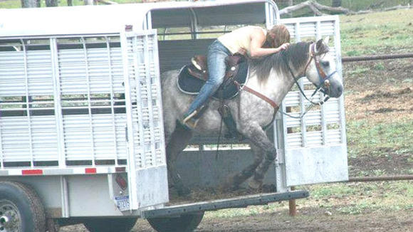Olivia Havel and her horse, Zans Gold Hickory, demonstrate their skills as she jumps out of a horse trailer on horseback during the Cowboy Challenge.