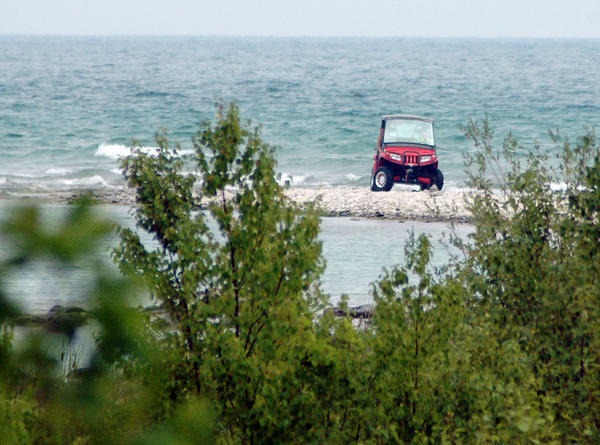 Search crew members drive a sheriff's office all-terrain vehicle on a spit of land near the end of McSauba Avenue in Charlevoix Township Tuesday moments before crews found Daniel Paul Engstrom, 54, alive on shore a short distance away.