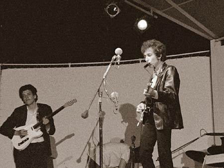 Bob Dylan, right, accompanied on July 25, 1965, at the Newport Folk Festival by a rock band that included guitarist Mike Bloomfield, left.