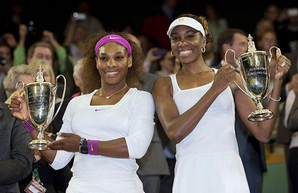 Serena Williams, left, and Venus Williams with their trophies in the women's doubles finals of the 2012 Wimbledon Championships at the All England Lawn Tennis Club.  Serena and Venus are from Palm Beach Gardens. Serena will play in singles and doubles while Venus will compete only in doubles.