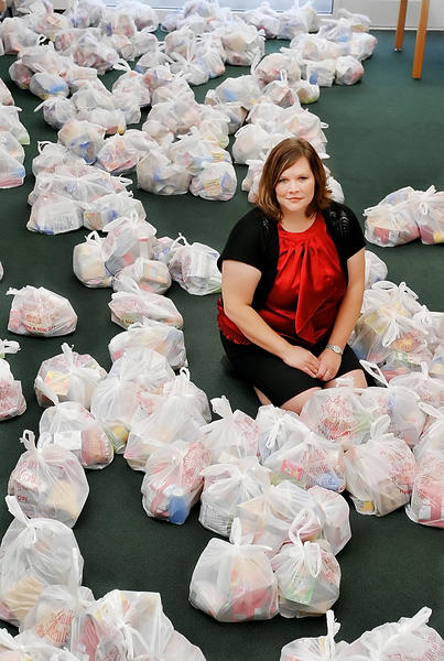 Misty Francis, missions coordinator for the Bags of Love (BOL) program of One Hope Ministries International, is surrounded by bags of food that will be given to needy children in Berkeley County, W.Va.