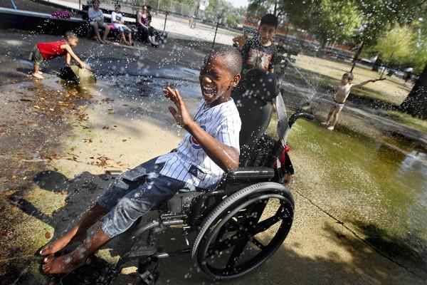 Amid near-record heat, Martrell Stevens, 8, cools off in a fountain at California Park on Tuesday. Martrell and his wheelchair softball teammates were cooling off after practice.