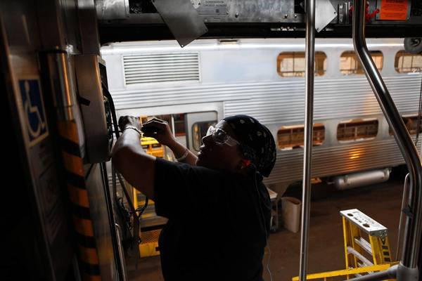 An electrician works on a panel of a rail car being refurbished as part of Metra's ongoing plan to save money by overhauling 1990s-era cars rather than replacing them. The new amenities on the passenger coaches include improved toilets and doors as well as better seating and air conditioning. The rehabs run around $650,000 apiece, versus millions for a new car.
