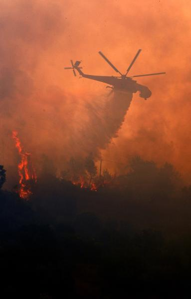 A firefighting helicopter sprays water on a forest fire near the city of Patras, some 200 kilometers southwest of Athens.