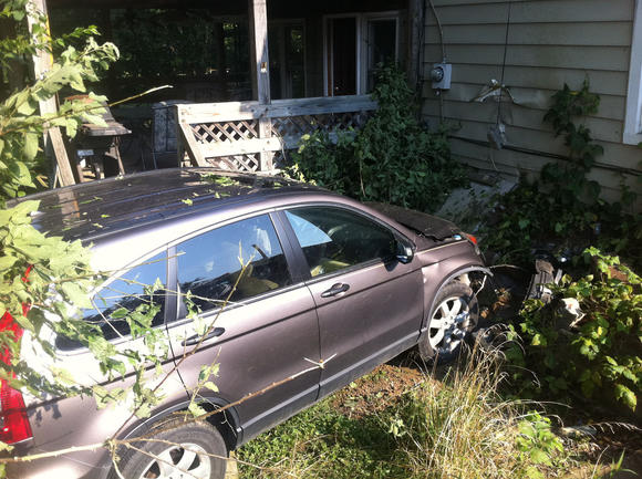 SUV crashes against house