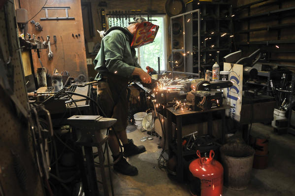 Ed Kidera, a longtime metal sculptor, creates a hook for a bell at his workshop in his home in Woodbine.