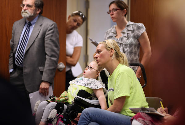 Myra Young, of Chicago, with her four-year-old daughter Letty, attends a meeting about changes in a program that helps kids with complex medical needs.