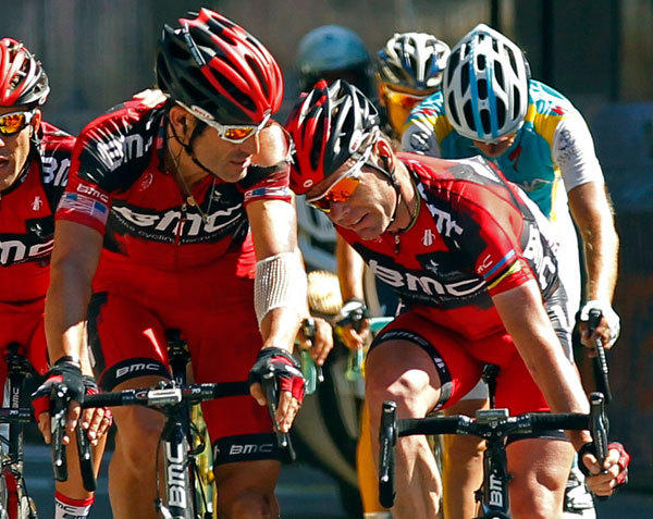 BMC Racing Team rider Cadel Evans of Australia (R) is helped by team mate George Hincapie of the U.S. (C) on the finish line of the 16th stage of the 99th Tour de France cycling race between Pau and Bagneres-de-Luchon, July 18, 2012.