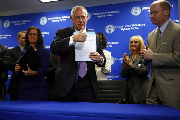 Gov. Pat Quinn gives the sign of approval for the consumer protection legislation that will protect consumers from false phone charges. Attorney General Lisa Madigan, left, and State Sen. Don Harmon, D-Oak Park, right, joined him at the press conference at the Citizens Utility Board today.