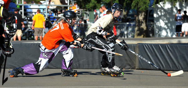 Modern Amish's Chris Tancozos 15, left, of Point Phillips, chases VooDoo's Morgan Singer, 15, of Breinigsville during a roller hockey game held on Day 3 of SportsFest at Cedar Beach Park on Saturday, July 16, 2011.