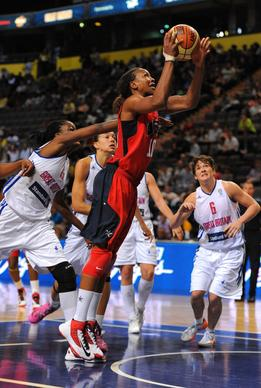 Tamika Catchings (C) of the USA  womens Olympic basketball scores a basket during their Olympic warm up game against Great Britain at the Manchester Arena in Manchester, north-west England on July 18, 2012.