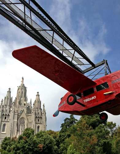 "Among Barcelona's many jewels is the retro Tibidabo amusement park, where visitors can take a ""ride"" in a vintage plane. The Church of the Sacred Heart in the distance is perhaps a comfort to nervous fliers."