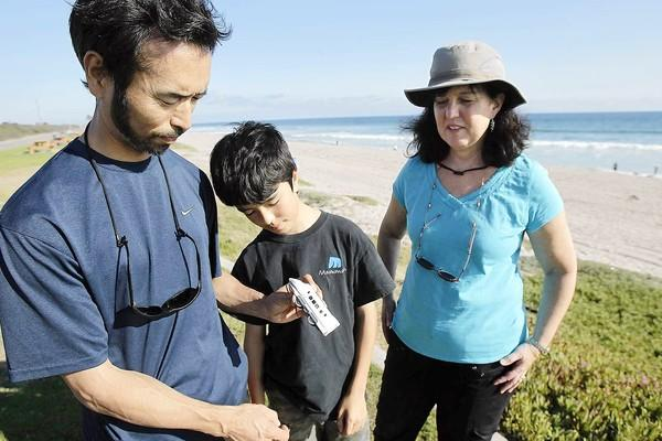 Yuji Kaneko with his son, Ryan, and wife, Beverly, talk about a Komachi toy train car they found in Huntington Beach and suspect drifted from Japan following the 2011 tsunami.