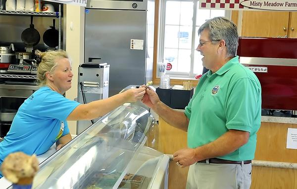 Betsy Herbst hands a spoon of ice cream to Maryland Secretary of Agriculture Buddy Hance during his visit to Misty Meadow Farm Creamery near Ringgold on Wednesday.