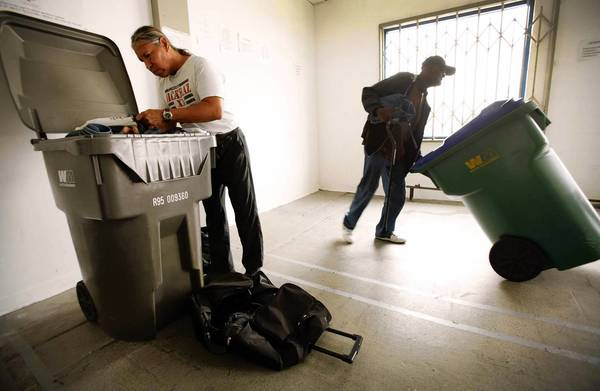 Newton Burr, left, organizes his belongings in a converted trash bin while Ed Richmond, right, wheels his bin back to the storage area at the downtown Los Angeles Check-In Center, which is operated by the Central City East Assn. business improvement district and provides homeless residents a place to keep their things. Cash-strapped cities throughout California are struggling with the spread of encampments and the ramifications of clearing them out.