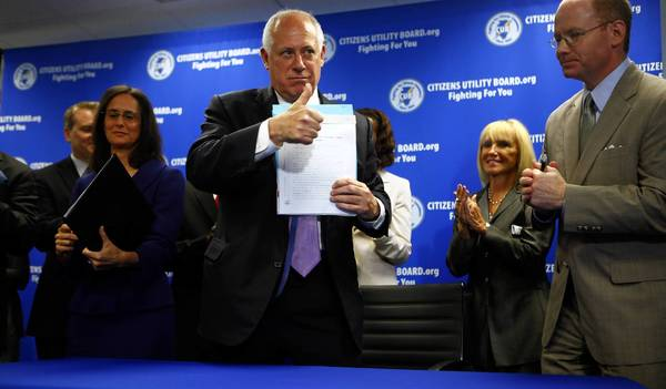 Gov. Pat Quinn signs consumer protection legislation, including a bill protecting consumers from false phone charges, at the Citizens Utility Board on Wednesday with Attorney General Lisa Madigan and state Sen. Don Harmon, D-Oak Park.