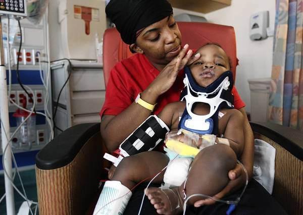 Tiesha Powell holds her son, Kyan, at Comer Children's Hospital at the University of Chicago on Wednesday after the 10-month-old fell from a third-story window at their home in Gary.