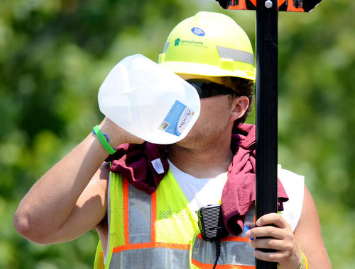 Korbin Price of Orefield, a PennDot worker, cools off with water as he  directs traffic on the Race Street Bridge Wednesday afternoon in 90-degree-plus temperatures. His crew was painting lines on the road