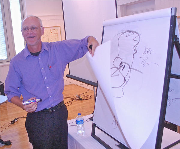 Pulitzer Prize-winning editorial cartoonist Joel Pett turns the page on a drawing of former President George H.W. Bush during his visit Wednesday to the Community Arts Center in Danville.
