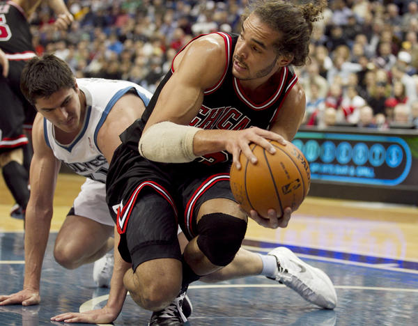 Minnesota's Darko Milicic stumbles as he battles Joakim Noah for a loose ball in January.