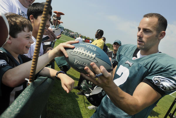 Dylan Cooper, 13, of Ambler, gives a football to Eagles' specialist, #2, David Akers (from left) to sign at training camp. The first full day of Eagles training camp with all Eagles players took place Saturday morning at Lehigh University.