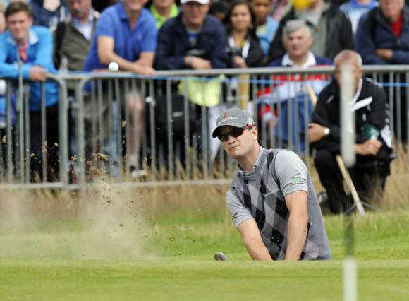 Zach Johnson plays out of a bunker on the first day of The British Open.