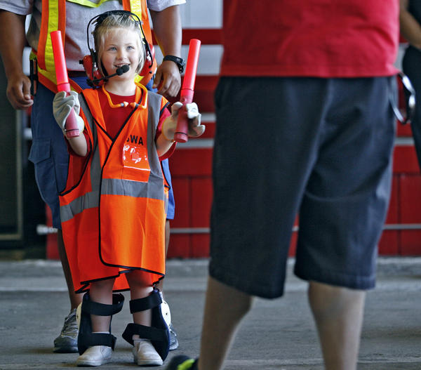Wearing Southwest Airlines ground crew equipment, 6-year-old Emmy De Oliveira learns how to guide an airplane using a person during the Robert Gross Park Camp visit to the Bob Hope Airport in Burbank on Thursday, July 19, 2012. Sixty-five children visited the airport's fire station and learned about airport careers.