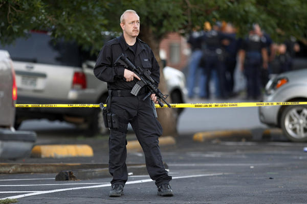 A SWAT officer stands watch with an automatic rifle near the apartment house where the suspect in the shooting lived.
