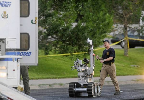 Photos: Shootings at Colorado theater: The Aurora, Colorado bomb squad robot is deployed to search a suspects car behind the Century 16 Theatre following a shooting during a Batman movie screening.