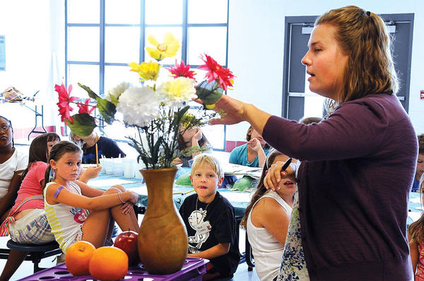 Allison Swanner explains how to draw a still life of a vase, flowers and fruit during the Exceptional Artist Art Camp she taught this week at Clark Middle School.