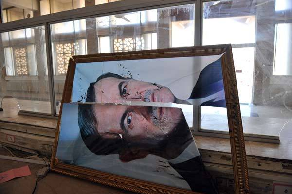A broken picture of former Syrian president Hafez al-Assad is seen at the Bab Al-Hawa border gate after clashes between Syrian rebels and the Syrian Army on July 20, 2012.