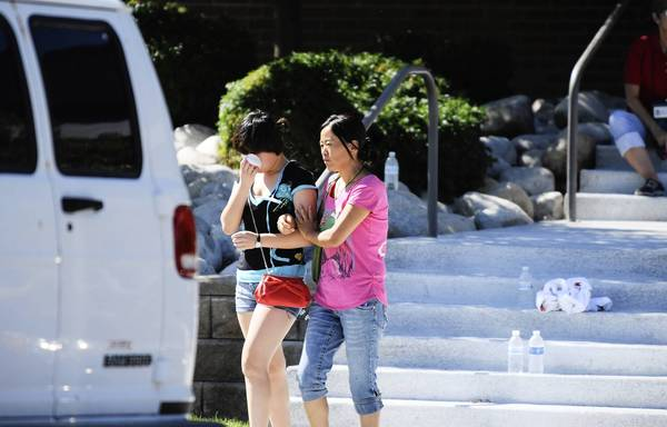 Photos: Shootings at Colorado theater: Lin Gan wipes away her tears as her mother Juan Gan guides her to their car after meeting with counselors at the Gateway High School in Aurora, Colorado where families are meeting after the Century 16 theater massacre where a gunman opened fire on the audience during the new Batman movie.