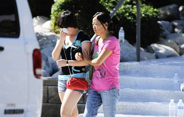 Lin Gan wipes away her tears as her mother Juan Gan guides her to their car after meeting with counselors at the Gateway High School in Aurora, Colorado where families are meeting after the Century 16 theater massacre where a gunman opened fire on the audience during the new Batman movie.