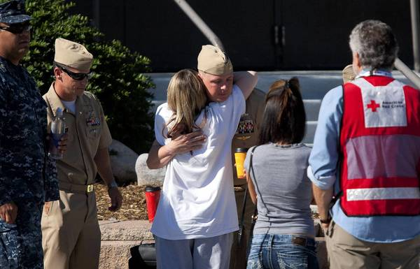 Photos: Shootings at Colorado theater: A woman is comforted by members of the military after trying to learn the fate of her loved ones outside Gateway High School in Aurora, Colorado. Twelve people were killed and dozens wounded, according to police.