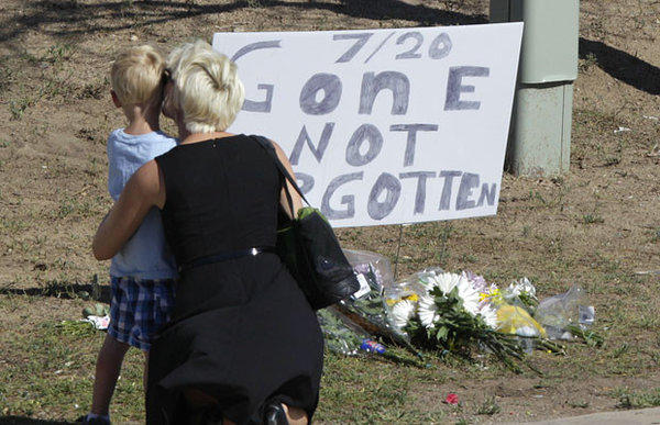 "A woman and a child stand near a sign that reads, ""7/20 Gone Not Forgotten,"" near the movie theater where a gunman killed at least 12 people and wounded dozens of others in Aurora, Colo."