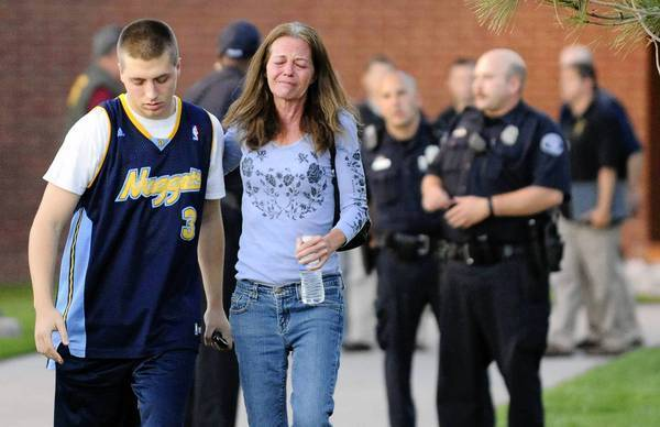 Eyewitness Jacob Stevens, 18, and his mother, Tammi Stevens, walk away after police interviewed Jacob about the Aurora, Colo., shootings. Other families waited for news.