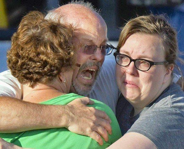 "Tom Sullivan hugs relatives at Gateway High School, where he was seeking information on his son, Alex, who went to see ""The Dark Knight Rises"" for his birthday. Some victims remained unidentified Friday."