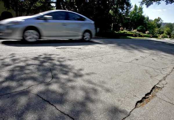 The road on the 4400 block of Woodleigh is cracked and has potholes.