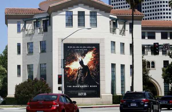 "A movie poster promoting the new Batman movie hangs on a building across from the Warner Bros. studios in Burbank on Friday. A massacre occurred in a movie theater in Aurora Colorado at the midnight showing of ""The Dark Knight Rises."""