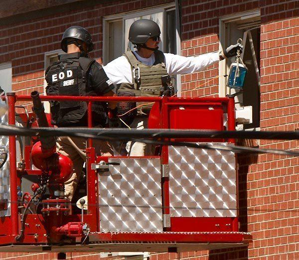A bomb disposal squad inserts an explosive device into the apartment of mass shooting suspect James Holmes in Aurora, Colo., to destroy some of the booby traps and trip wires left behind.