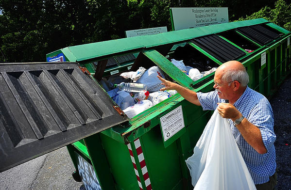 Kevin Bearese tosses plastics into recycling bin Thursday at Greensburg Convenience Center near Smithsburg.