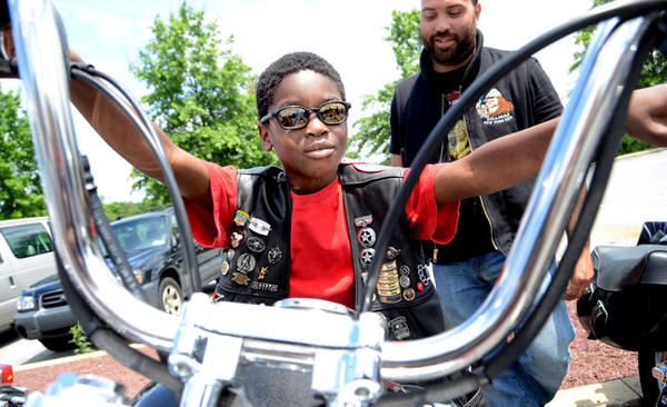 Tyaire Carson, 8, enjoys the feel of sitting on the motorcycle of Denis Borhi of Queens, New York, right. 50 bikers belonging to the group Independent Bikers of Pennsylvania made their 11th annual Christmas in July ride to KidsPeace Saturday, bringing gifts to the residents.