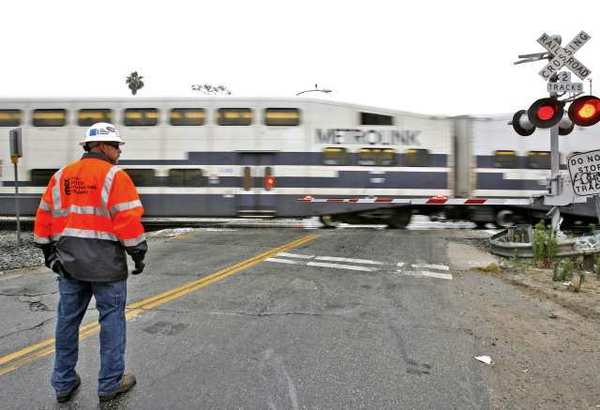 A Metrolink employee keeps an eye on traffic as a train passes by the Doran Street and San Fernando Road crossing in Glendale.
