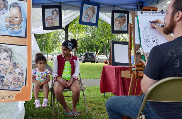 "Aaliyah Ross, left, 3, and big sister Amillion Black, 10, both of Salisbury pose for their caricature to be drawn by Alexander Clare in his ""Alexander the Art"" tent during Emmaus Parks and Recreation Commission's Community Day on Saturday, July 21 at Emmaus Community Park. The event included games, music, and food."