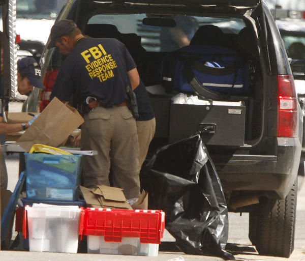 FBI investigators look over some of the items taken from suspect James Holmes' apartment in Aurora, Colo.