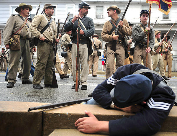 Confederate soldiers reload on Baltimore Street in Funkstown while battling with Union soldiers Saturday during the re-enactment of the Civil War battle at Funkstown.