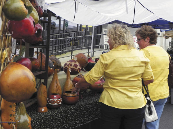 Longtime friends Sherry Wenger and Bonnie Marpoe, both of Shippensburg, Pa., stop to admire some unique carved gourds on Saturday at Celebrate! The Arts at Old Market Day in Chambersburg, Pa.